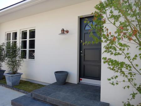 STORKEのネイビーグレーのドアと白い壁でオープンな玄関に